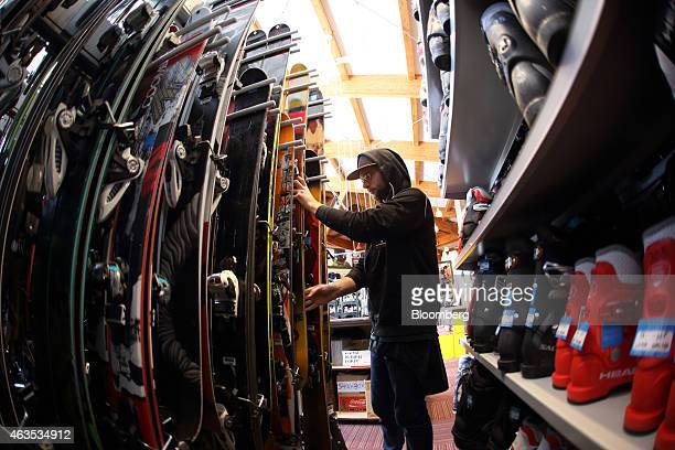 An employee arranges ski in this photograph taken with a fisheye lens inside a rental ski shop at the Niseko Hanazono resort operated by Nihon...