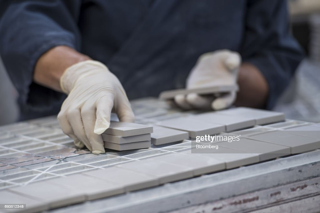 An employee arranges tile squares to be glazed at the Heath