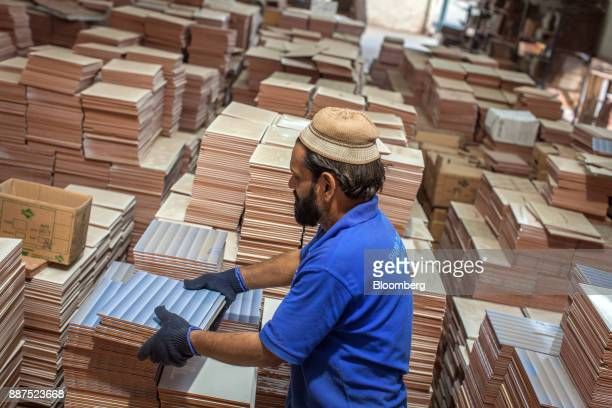 An employee arranges tiles before packing into the boxes at the Shabbir Tiles Ceramics Ltd production facility in Karachi Pakistan on Wednesday Dec 6...
