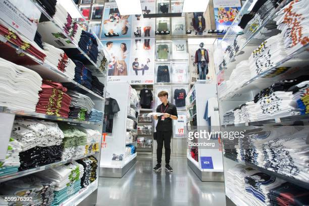 An employee arranges tshirts displayed for sale at a Uniqlo store operated by Fast Retailing Co in the Orchard Central shopping mall in Singapore on...