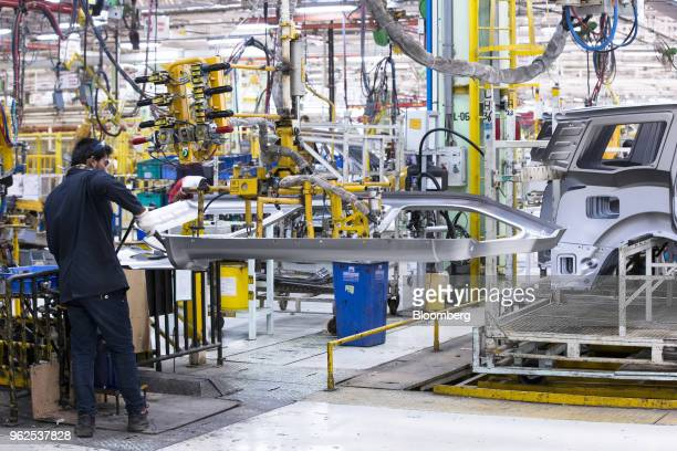 An employee assembles a door plate for a Mahindra Mahindra Ltd XUV 500 sportutility vehicle on the production line at the company's facility in...