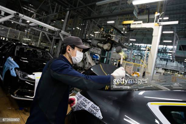 An employee assembles a Hyundai Motor Co Genesis luxury sedan on the production line at the company's plant in Ulsan South Korea on Monday April 24...