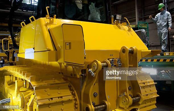 An employee assembles a Komatsu Ltd excavator on the production line of the company's plant in Hirakata City Osaka Japan on Thursday Feb 23 2012...