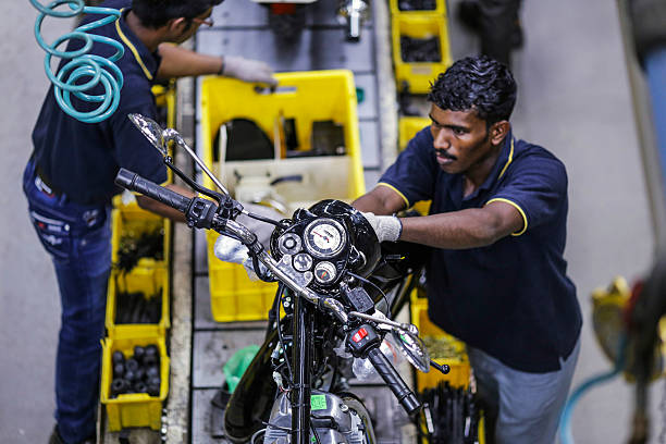 An employee assembles a Royal Enfield Motors Ltd Classic 350 motorcycle moving on a conveyor on the production line at the company`s manufacturing...