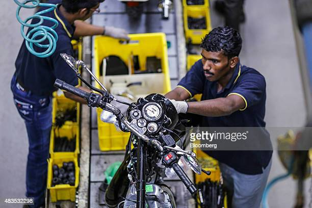 An employee assembles a Royal Enfield Motors Ltd. Classic 350 motorcycle moving on a conveyor on the production line at the company's manufacturing...