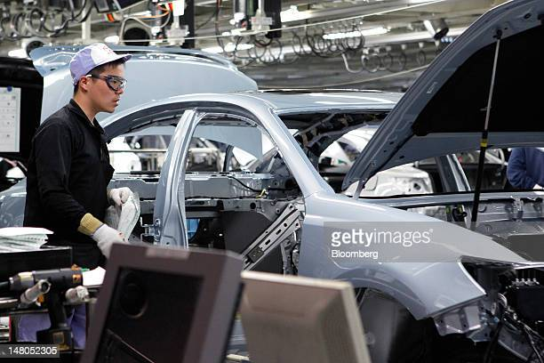 An employee assembles a Toyota Motor Corp Lexus vehicle on the production line of Toyota Motor Kyushu Inc's Miyata plant in Miyawaka City Fukuoka...