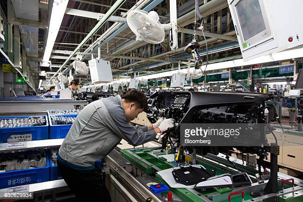 An employee assembles a vehicle dashboard module on the production line at the Hyundai Mobis Co factory in Asan South Chungcheong South Korea on...