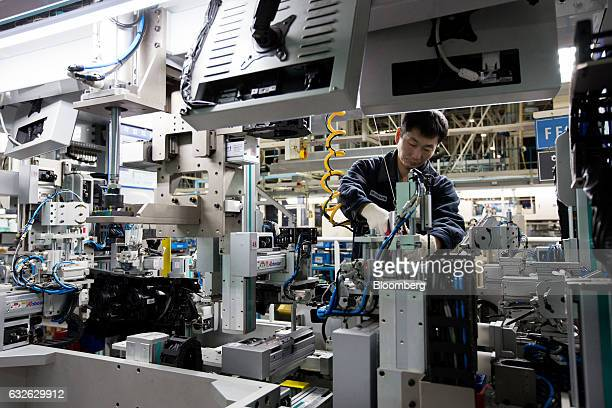 An employee assembles a vehicle frontend module on a production line at the Hyundai Mobis Co factory in Asan South Chungcheong South Korea on Tuesday...