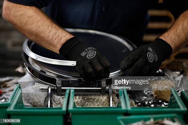 An employee assembles an oven hob plate for an AGA range cooker produced by AGA Rangemaster Plc during the manufacturing process at the company's...