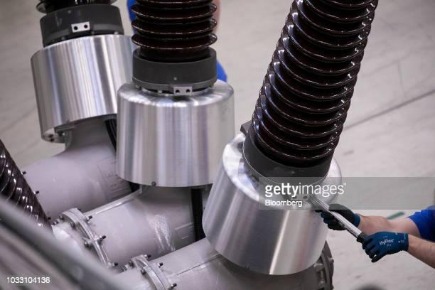An employee assembles dead tank circuit breaker brushings on the production line inside Siemens AG switchgear electronic power unit factory in Berlin...