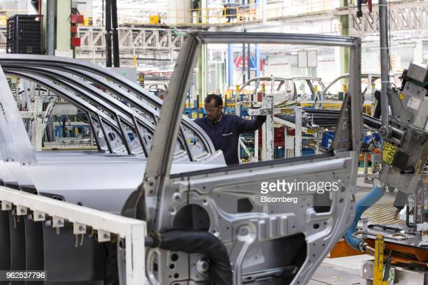 An employee assembles door plates for Mahindra Mahindra Ltd XUV 500 sportutility vehicles on the production line at the company's facility in Chakan...