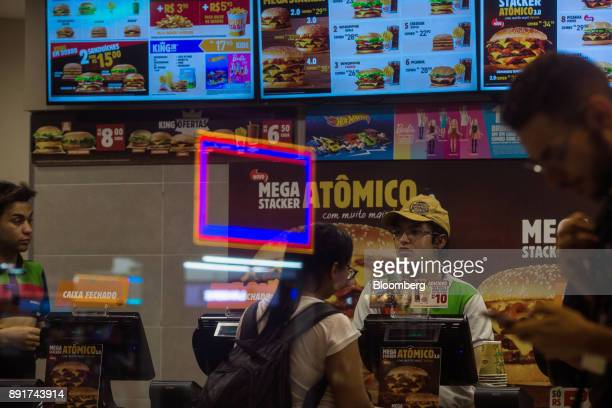 An employee assists a customer at a Burger King do Brasil restaurant in Sao Paulo, Brazil, on Monday, Dec. 11, 2017. Burger King do Brasil may raise...