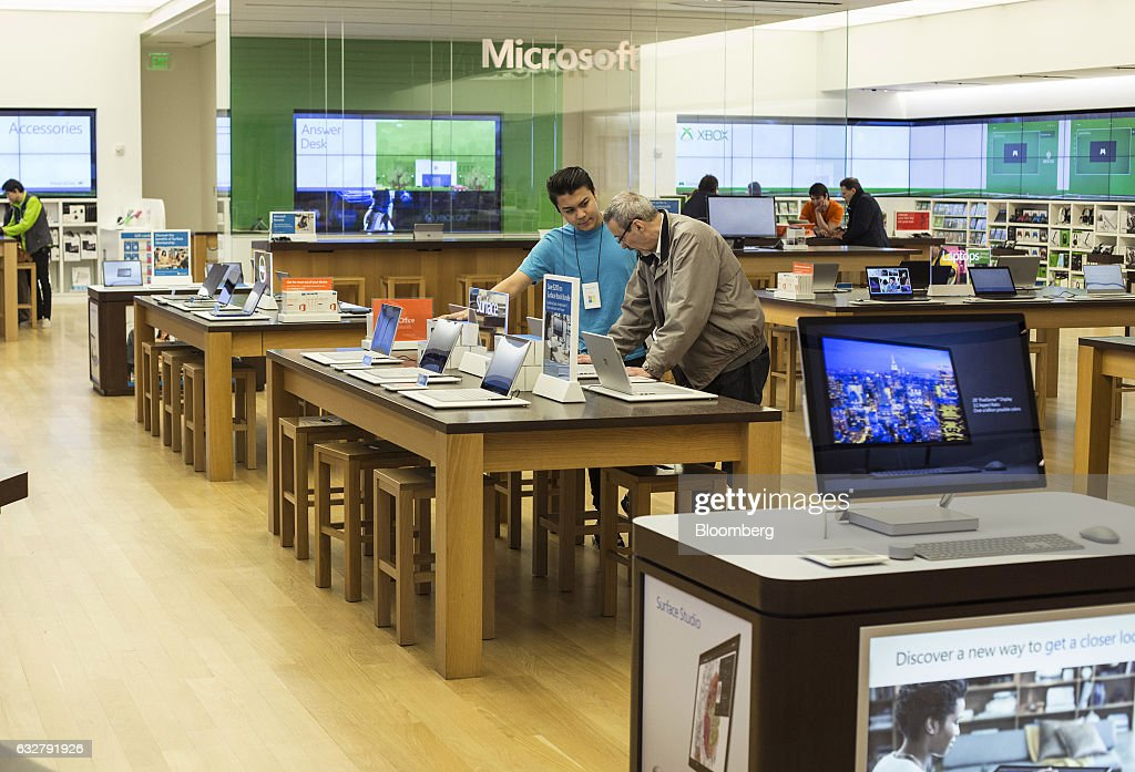 An employee assists a customer at a Microsoft Corp. store in Bellevue, Washington, U.S., on Thursday, Jan. 26, 2017. Microsoft Corp.'s second-quarter sales and profit exceeded analysts' projections, bolstered by rising customer sign-ups for Azure and Office cloud-computing services. Photographer: David Ryder/Bloomberg via Getty Images