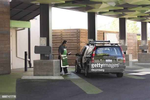 An employee assists a customer at an AmazonFresh Pickup location in Seattle Washington US on Friday May 26 2017 Amazoncom Inc opened two grocery...