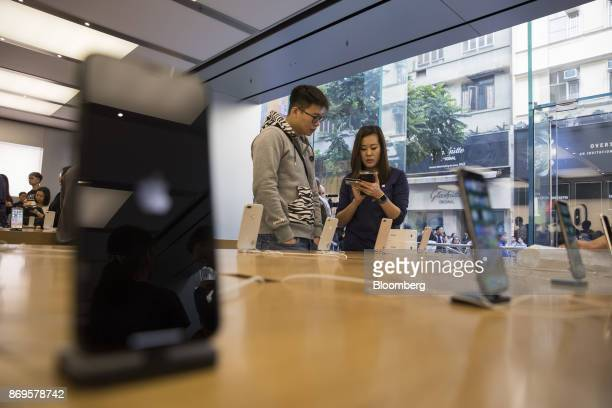 An employee assists a customer purchasing the Apple Inc iPhone X at an Apple store during its launch in Hong Kong China on Friday Nov 3 2017 Long...