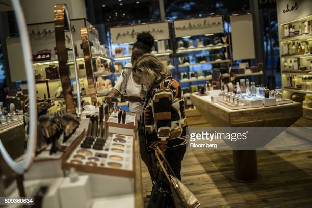 An employee assists a customer viewing makeup on display at a Natura Cosmeticos SA store inside the Santos Dumont Airport in Rio de Janeiro Brazil on...