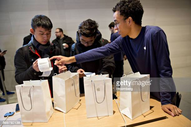 An employee assists a customer who purchased four Apple Inc iPhone X smartphones during the sales launch at a store in Chicago Illinois US on Friday...