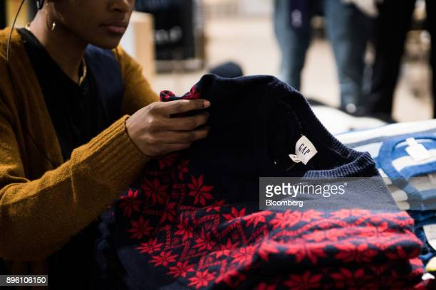 An employee assists a customer with a sweater displayed for sale at a Gap Inc store in New York US on Wednesday Dec 13 2017 Bloomberg is scheduled to...