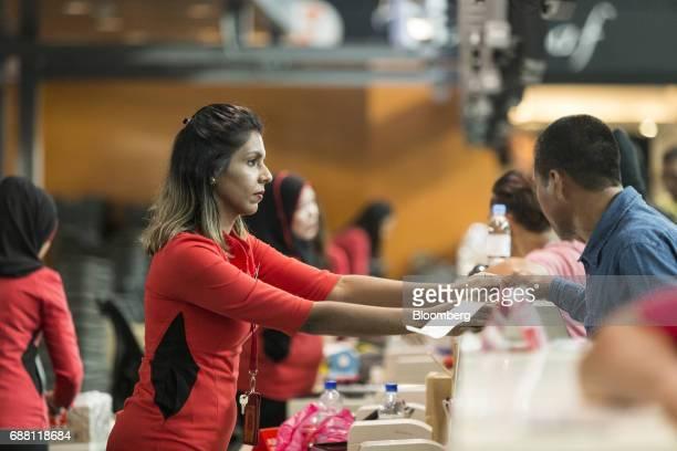An employee assists customers at an AirAsia Bhd checkin counter at Kuala Lumpur International Airport 2 in Sepang Selangor Malaysia on Thursday May...