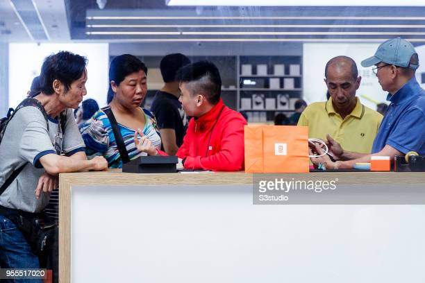 An employee assists customers inside of the Xiaomi Corp store on Nathan Road in Hong Kong on May 7 2018 in Hong Kong Hong Kong A report by Strategic...
