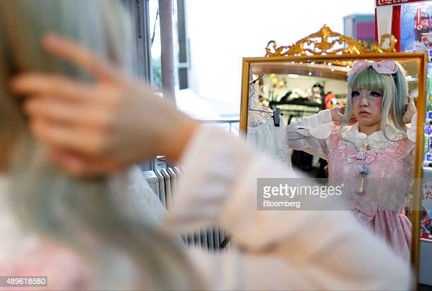 An employee at a clothing store looks in a mirror while adjusting her hair on Takeshita Street in the Harajuku area of Tokyo Japan on Tuesday Sept 22...