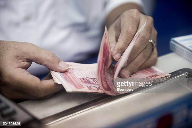 An employee at a currency exchange store counts Chinese onehundred yuan banknotes in Hong Kong China on Tuesday Jan 12 2016 China stepped up its...