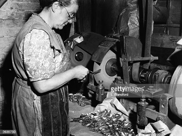 An employee at a factory in Sheffield finishes the prongs of a fork, already roughly cut by machinery, by grinding them on a thin wheel.