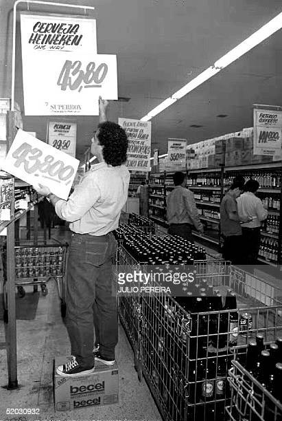 An employee at a local supermarket puts up new price signs 02 August 1993 as Brazil changes its currency from Cruzeiro to Real Cruzeiro in a bid to...