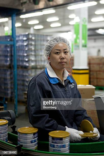 An employee at a Nestle SA plant poses for a portrait in Shuangcheng Heilongjiang Province China on Wednesday Jan 11 2012 Nestle will spend 25...
