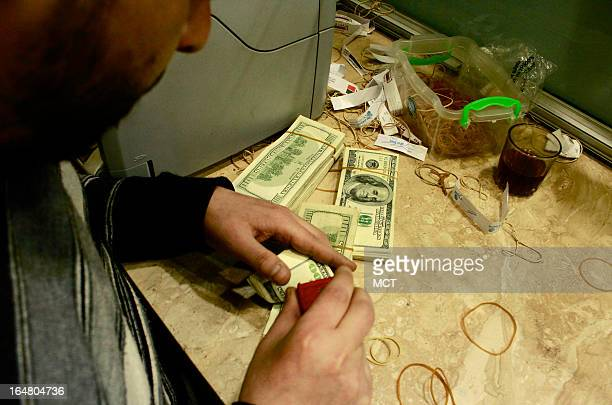 An employee at a registered foreign exchange office in downtown Cairo stamps dollars for a client Banks restrict the amount of dollars a client can...
