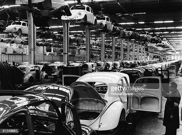 An employee at a Volkswagen plant work inspects a Volkswagen 1200 Sedan better known as a Beetle on the assembly line Wolfsburg Germany 1960s
