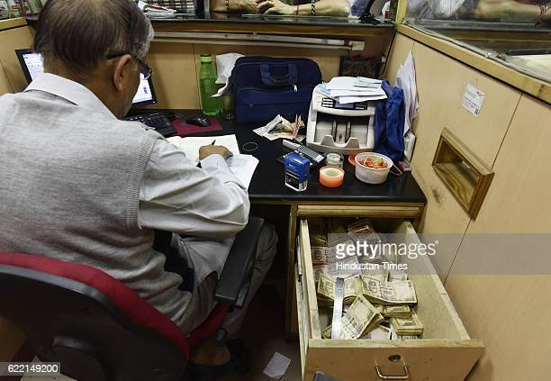 An employee at an exchange counter for old currency at Allahabad Bank branch of Parliament Street on November 10 2016 in New Delhi India It was a...
