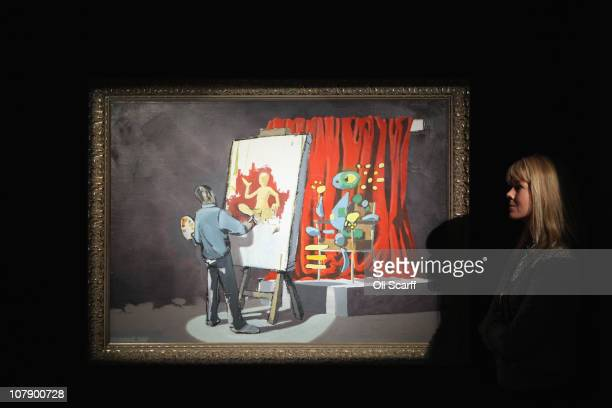 An employee at Bonhams auction house admires a painting by artist Banksy entitled 'Portrait of an Artist' on January 6, 2011 in London, England. The...