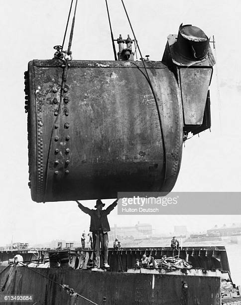 An employee at Cashmore's shipyard stands beneath a 30 ton boiler as it is hoisted from the hull of the scrapped liner India City.