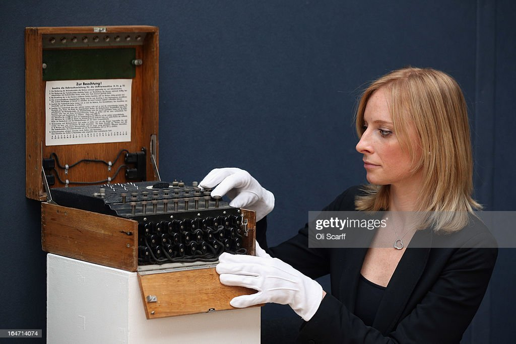 An employee at Christie's auction house examines an Enigma cipher machine on March 27, 2013 in London, England. The Enigma machine is expected to fetch 60,000 GBP when it features in Christie's 'Travel, Science and Natural History' sale, which is to be held on April 24, 2013 in London.