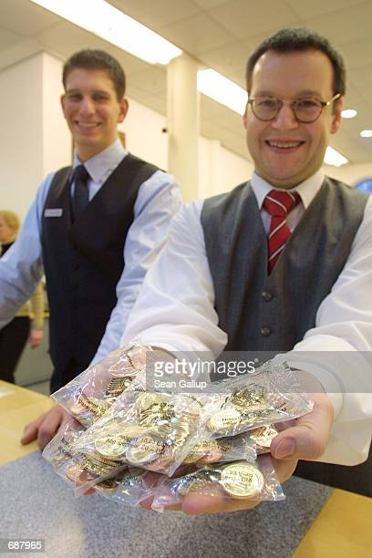 An employee at Dresdner Bank holds bags of Euro coins December 17 2001 in Frankfurt Germany the day banks started distributing the first socalled...
