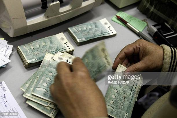 MOUSSAOUI An employee at Lebanon's Central Bank counts money bills at his office in Beirut on November 24 2008 Lebanon for now has managed to steer...