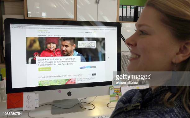 An employee at online platform betterplaceorg sits in front of computer screen displaying the start page of the new digital portal for refugees...