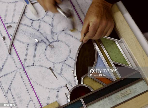 An employee at Serpentino Stained and Leaded Glass Studio works on a restoration for Trinity Church in Copley Square where there were more than 2000...