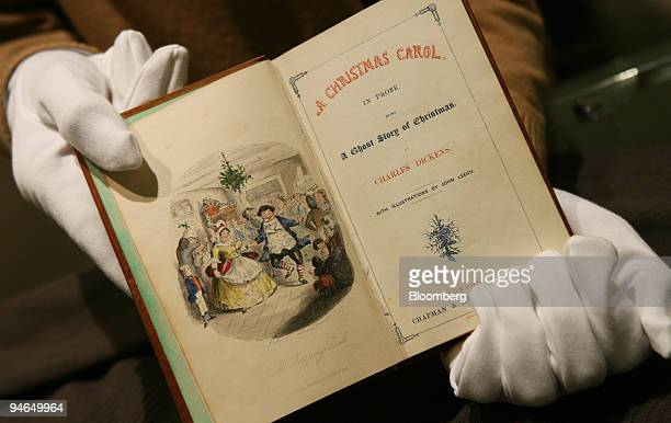 An employee at Sotheby's holds an 1843 first edition of the classic A Christmas Carol by Charles Dickens in London UK Tuesday December 5 2006 This...