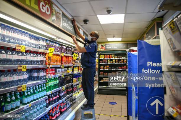 An employee at Tesco Plc, wearing a protective face mask, cleans inside a store in London, U.K., on Wednesday, April 22, 2020. Boris Johnson's...