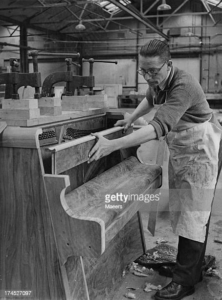 An employee at the Bentley piano factory assembles the cases around the sound board and frame Stroud Gloucestershire 22nd January 1946