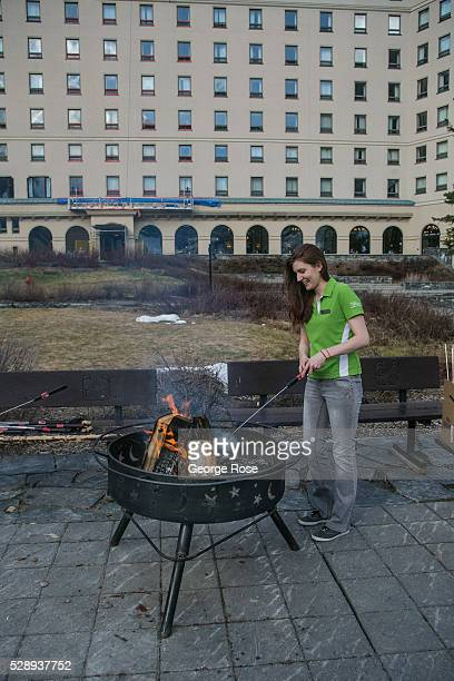 An employee at the Fairmont Chateau Lake Louise starts an outdoor fire pit on April 23 2016 at Lake Louise Alberta Canada Banff is Canada's oldest...