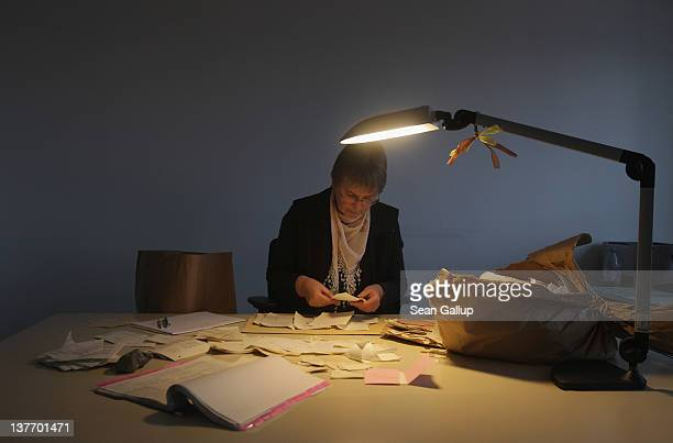 An employee at the federal archives of the former East German secret police the Stasi analyses torn remains of documents to determine their priority...