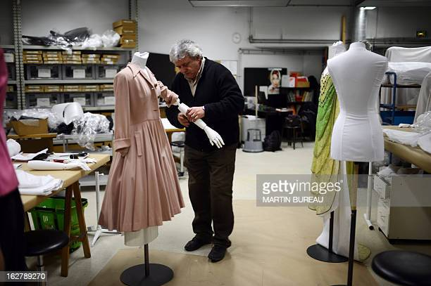 An employee at the Galliera museum works on a dress for the exhibition 'Paris Haute Couture' which will take place at the Hotel de Ville on January...