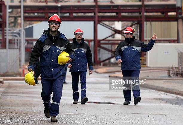 An employee at the Mytilineos Holdings SA aluminium smelting plant carries protective hard hats as he walks through the factory in Agios Nikolaos,...