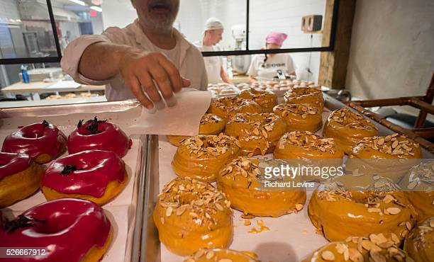 An employee at the new Dough bakery in the Flatiron neighborhood of New York serves a dulce de leche doughnut to a visitor on Thursday October 9 2014...