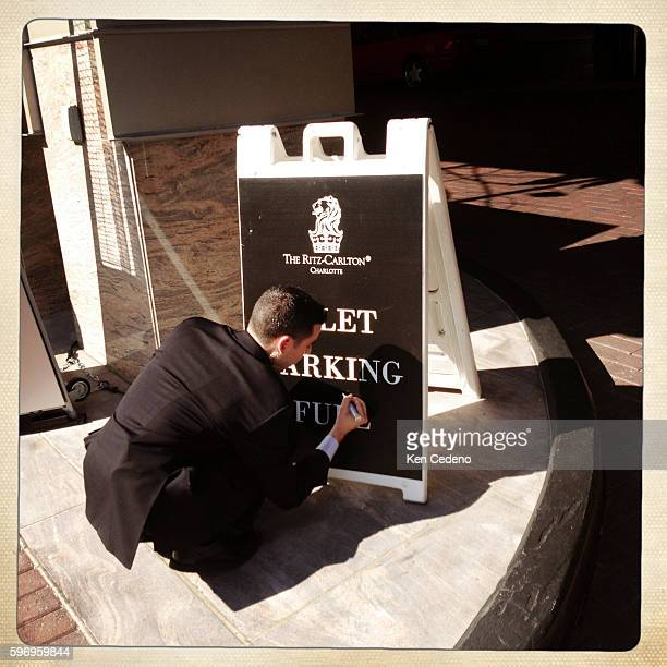 An employee at the Ritz Carlton uses a black sharpy to fill in the white marks on a Valet Parking sign near the Time Warner Arena August 31 2012 in...