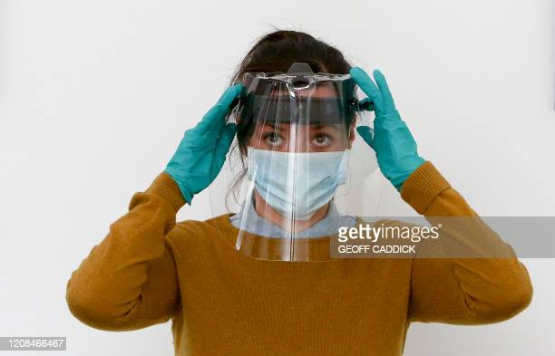 An employee at the Royal Mint poses for a photograph with a completed medical visor during a media opportunity at the company's plant in Pontyclun...