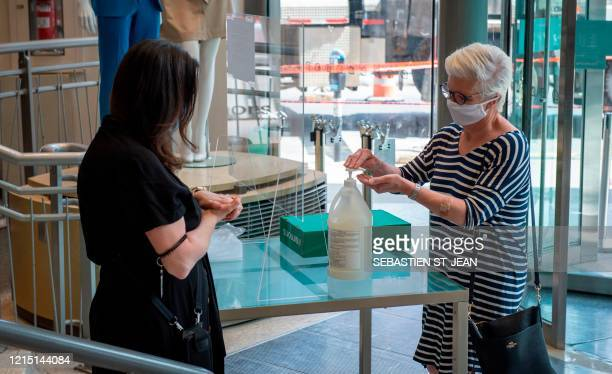An employee at the Simons store explains health safety procedures to a customer, both wearing facemasks, on Sainte-Catherine Street, in Montreal,...